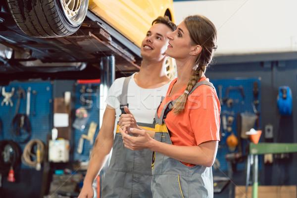 Two dedicated auto mechanics smiling while checking the wheels of a car Stock photo © Kzenon