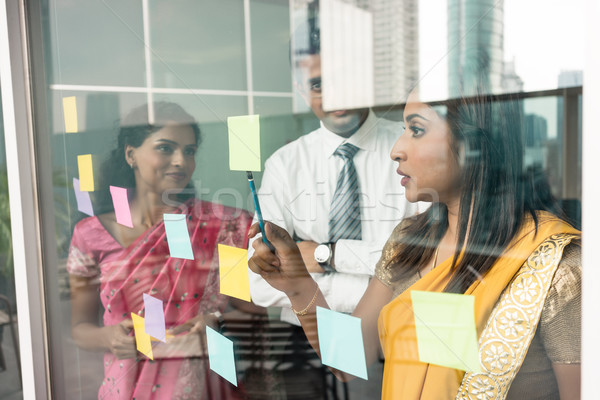 Indian employees sticking reminders on glass wall in the office Stock photo © Kzenon