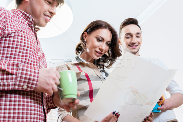 Men and woman in casual office looking at plan Stock photo © Kzenon
