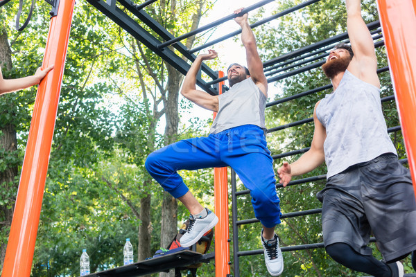 Stock photo: Two strong and competitive men exercising on monkey bars