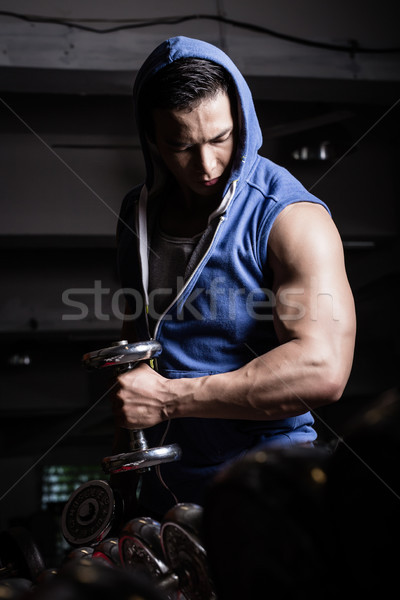 Young man reaching out with dumbbell in his hand Stock photo © Kzenon