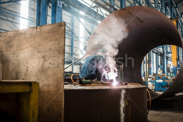 Blue-collar worker welding in the interior of a factory Stock photo © Kzenon