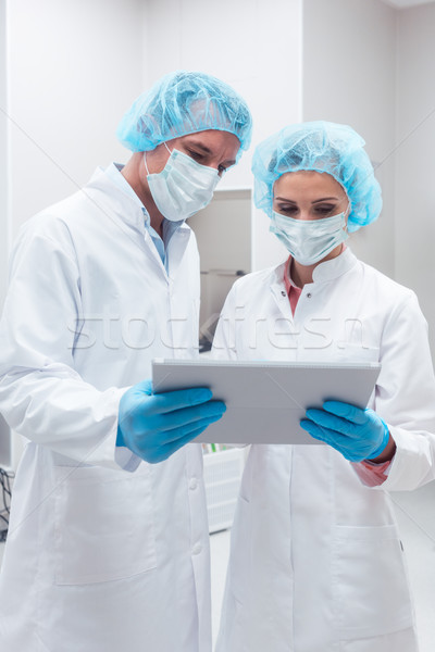 Stock photo: Two scientists working together in lab looking at data