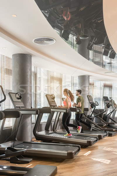 Stock photo: Young man and woman smiling while running side by side on treadmills