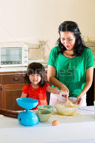 Asian Mother and daughter at home in kitchen Stock photo © Kzenon