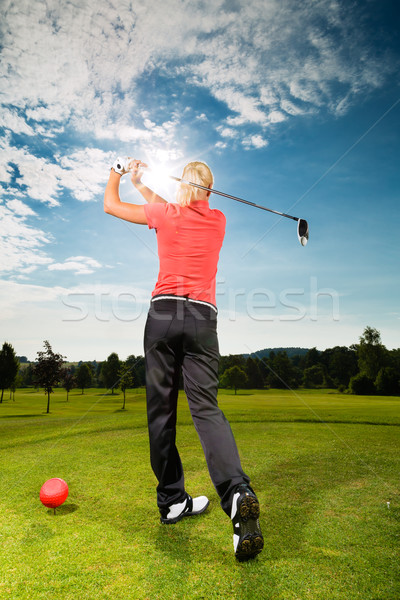 Young golf player on course doing golf swing Stock photo © Kzenon
