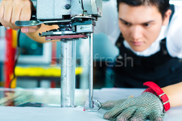 Worker using a machine in chinese factory Stock photo © Kzenon