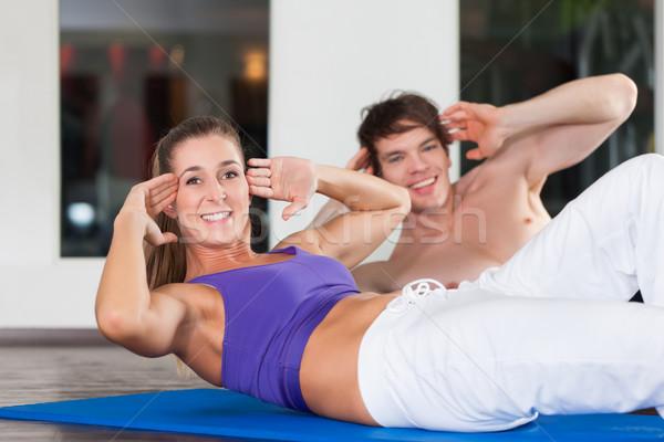Couple doing sit ups in gym Stock photo © Kzenon