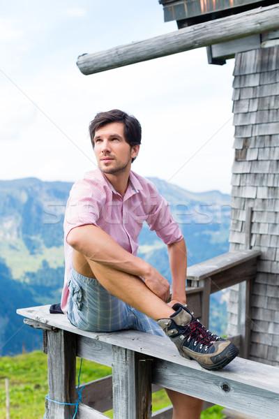 Alps - Man on mountains sitting at cabin in tirol Stock photo © Kzenon
