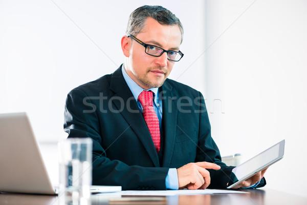 Businessman is working at office desk Stock photo © Kzenon