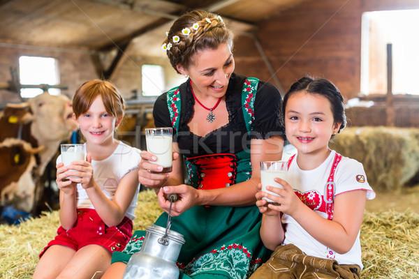 Bavaria family drinking milk in cow barn Stock photo © Kzenon