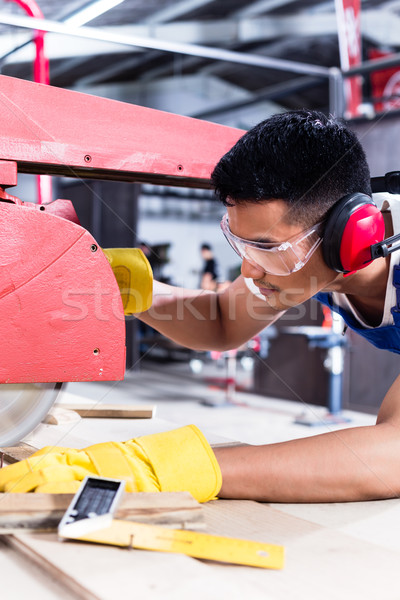 Carpenter in Asian workshop with circular saw Stock photo © Kzenon