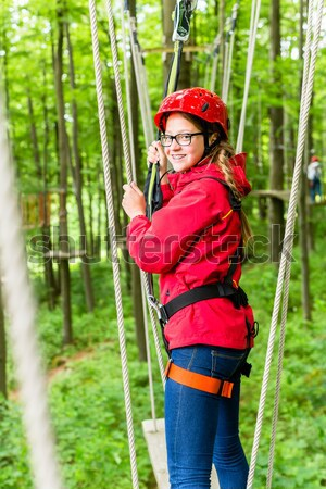 Woman in high rope course or park climbing Stock photo © Kzenon