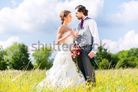 Wedding couple on meadow kissing Stock photo © Kzenon