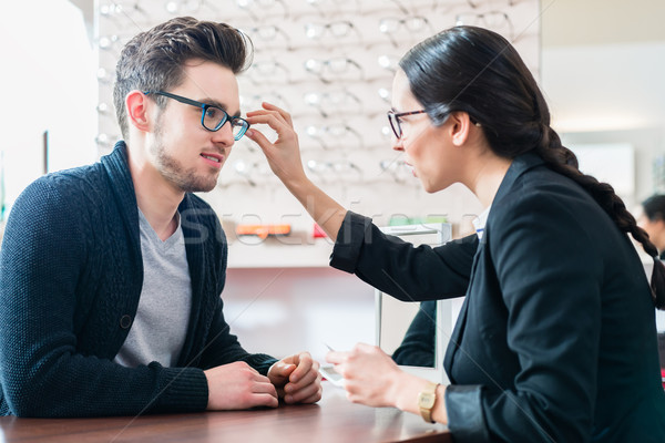 Man in optician shop getting advice from saleswoman Stock photo © Kzenon