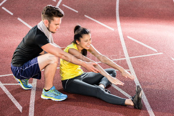 Man and woman on cinder track of sports arena stretching exercis Stock photo © Kzenon