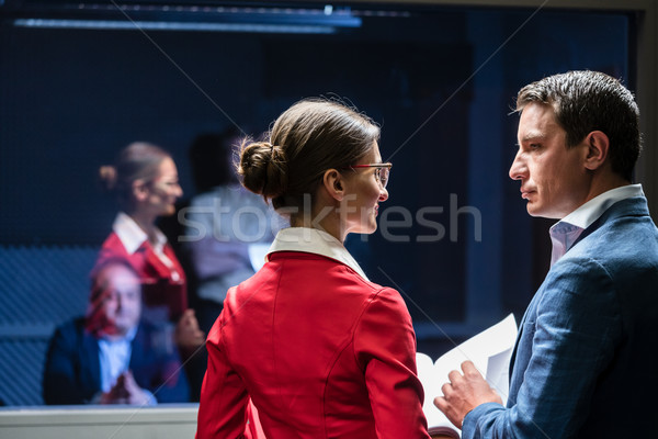 Stock photo: Two police detectives analyzing the files of a criminal case bef