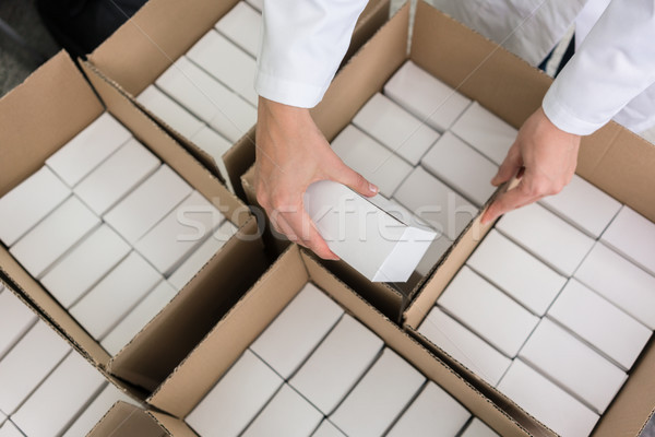 High-angle view of hands of worker putting packed products in ca Stock photo © Kzenon