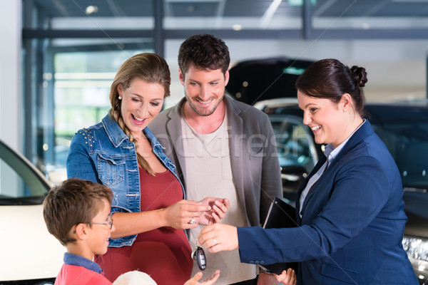 Car dealer giving key to new auto to family Stock photo © Kzenon
