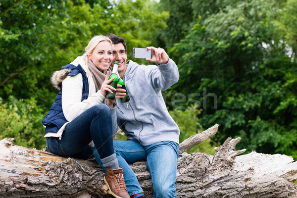 Woman and man drinking beer taking selfie while hiking Stock photo © Kzenon