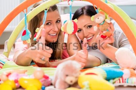 Women furnishing baby room preparing play bar for sucklings Stock photo © Kzenon