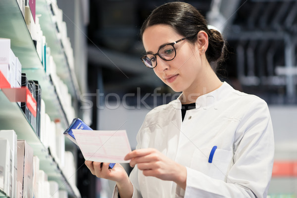 Low-angle portrait of female pharmacist checking a medical prescribtion Stock photo © Kzenon
