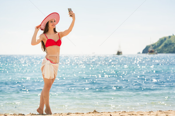 Beautiful young woman wearing a trendy striped hat while posing  Stock photo © Kzenon