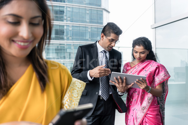 Stock photo: Three Indian business people using modern devices indoors