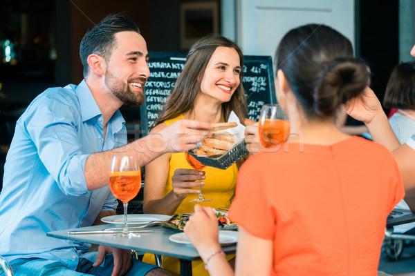 Cheerful friends toasting with a refreshing summer drink at a trendy restaurant Stock photo © Kzenon