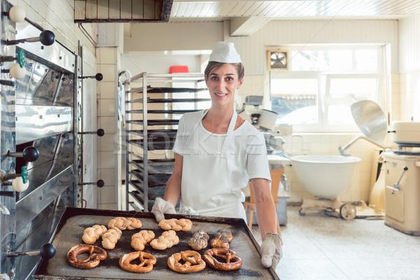 Baker showing her bread on tray in bakery Stock photo © Kzenon