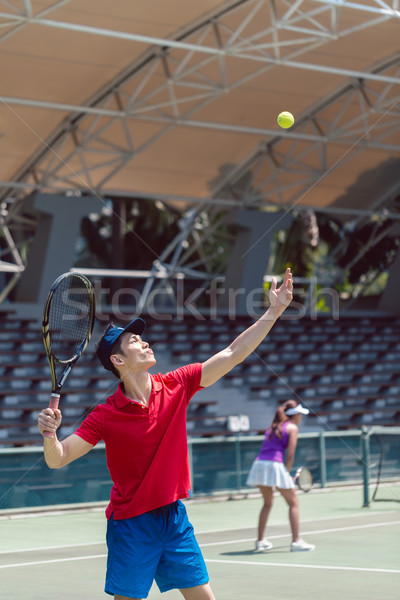 Asian tennis player ready to serve at the beginning of a doubles match Stock photo © Kzenon