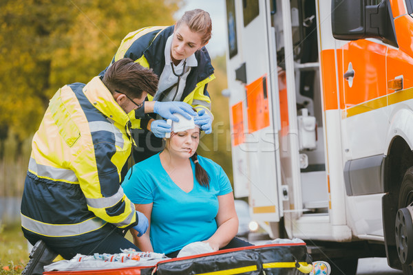 Emergency medics dressing head wound of injured woman Stock photo © Kzenon