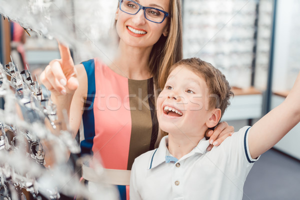 Mother and son both liking the eyeglasses offered in optician shop Stock photo © Kzenon