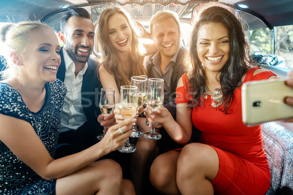Party people in a limo with drinks taking a selfie with phone Stock photo © Kzenon