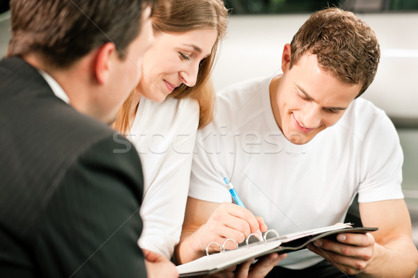 Couple signing sales contract at car dealer Stock photo © Kzenon
