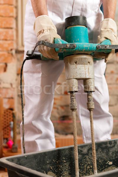 Construction worker mixing concrete Stock photo © Kzenon