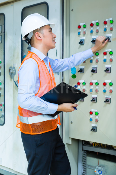 Asian technician at panel on construction site Stock photo © Kzenon