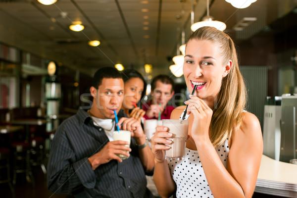 Stock photo: Friends drinking milkshakes in a bar