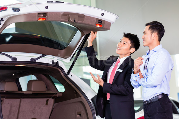 Asian man looking at car in dealership  Stock photo © Kzenon