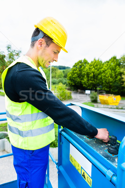 Crane driver driving hydraulic lifting ramp with control desk Stock photo © Kzenon
