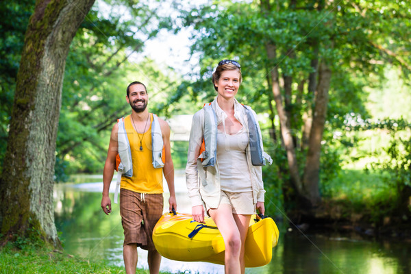 Man and woman carrying canoe to forest river Stock photo © Kzenon