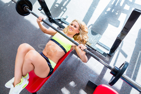 Woman at bench press in gym exercising for better fitness Stock photo © Kzenon