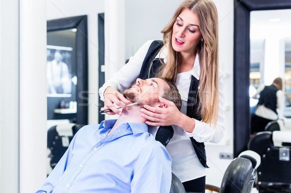 Man being shaved by barber woman Stock photo © Kzenon