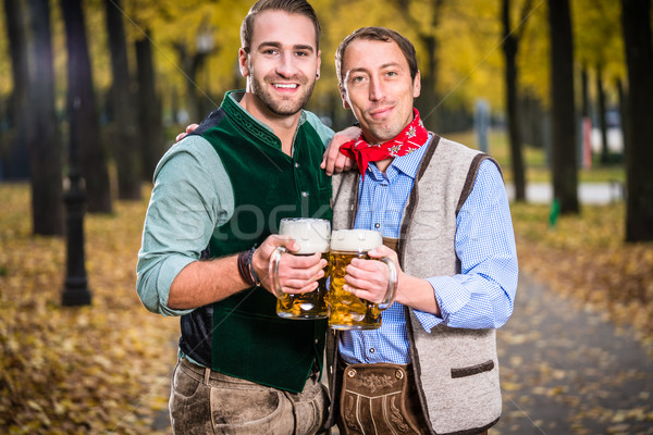 Men in bayrischer Tracht clinking glasses with beer Stock photo © Kzenon