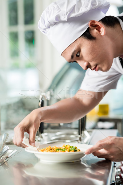 Handsome young Asian chef plating up food Stock photo © Kzenon
