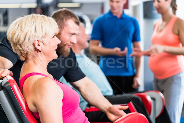 Stock photo: senior woman in group with pregnant woman working out at the gym