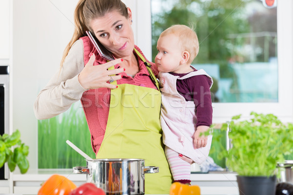 Mother having phone conversation during cooking and holding baby Stock photo © Kzenon