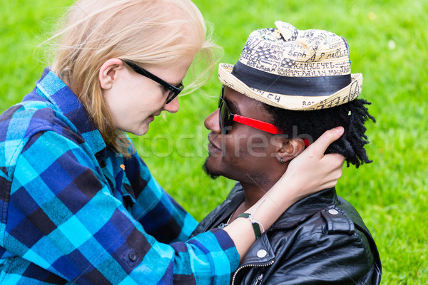 Caucasian woman and African man in loving embrace Stock photo © Kzenon