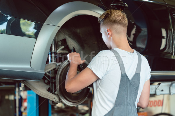 Experienced mechanic replacing the disk brakes of a car in a mod Stock photo © Kzenon