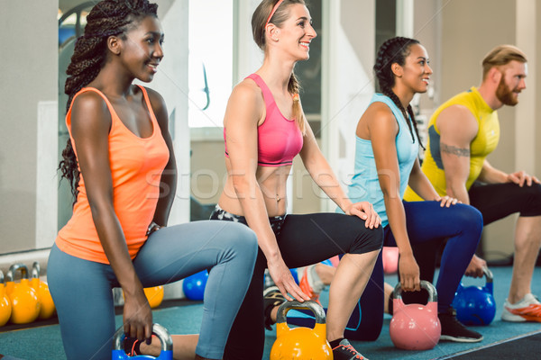 Three young people holding kettlebells during functional training Stock photo © Kzenon